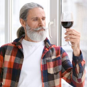 Senior man drinking wine ageing in place