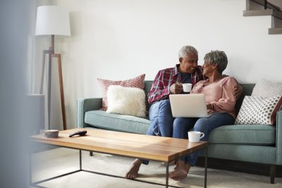 Senior Couple Sitting On Sofa At Home Using Laptop To Shop Online aging in place