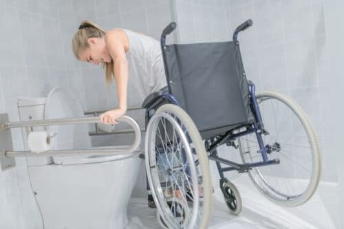 Wheelchair woman moving from chair to bathroom to meet her needs aging in place
